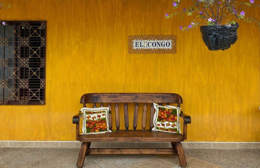 """fachada de una casa amarilla con azulejos que dicen """"El Congo"""" y una maceta colgando con flores moradas. Al frente hay una banca de madera con dos cojines"""