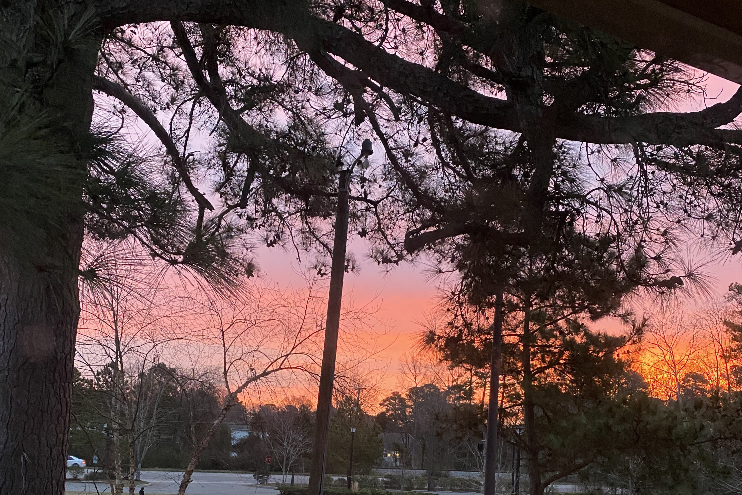 photo of the sun rising, tinting the sky with orange, pink, and purplish tones.